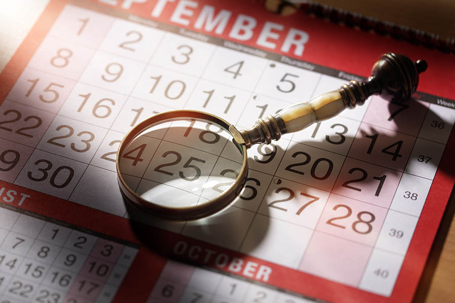 Calendar planning magnifying glass resting on an important date concept fpr deadline business appointment or meeting